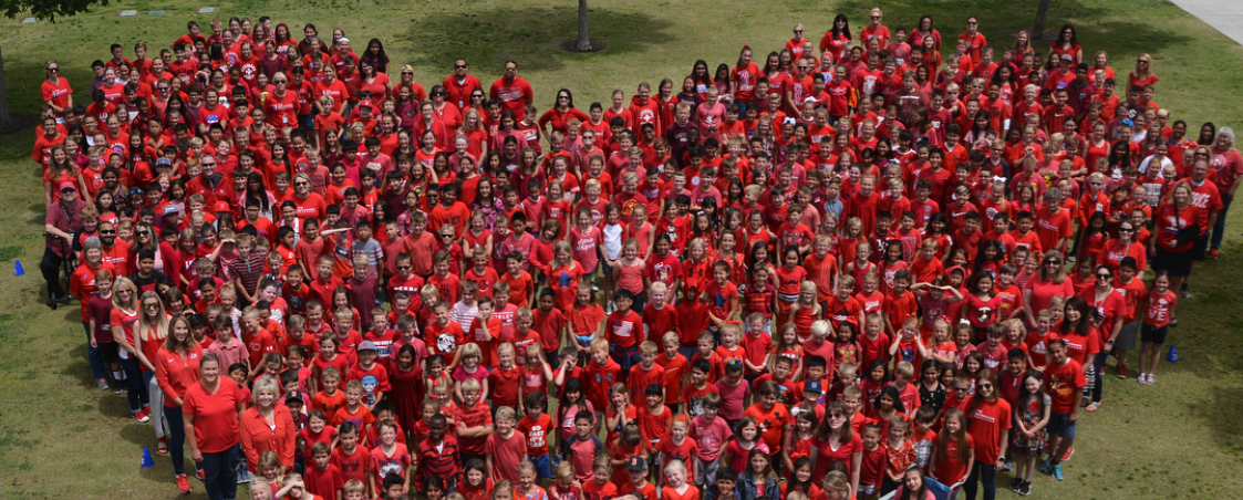 Students dressed in red forming the shape of a heart.